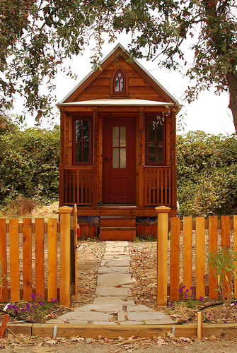 A tiny house with a picket fence.