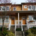 Yellow two-story duplex in Seattle, with stairs to a porch with white wooden railings.