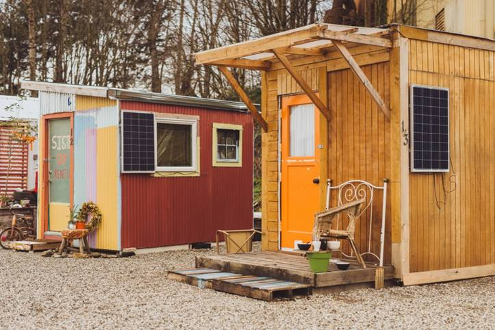 Photo of two well-kept tiny homes in a row on an otherwise undeveloped lot