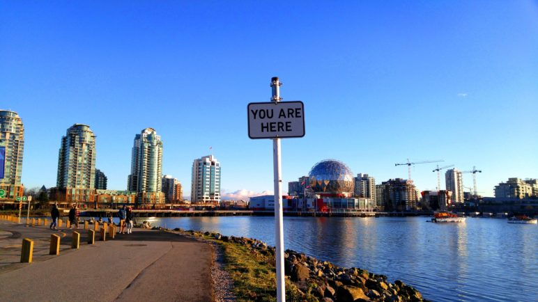 """Image of a sign saying """"You are here"""" along a path with downtown Vancouver BC in the background"""