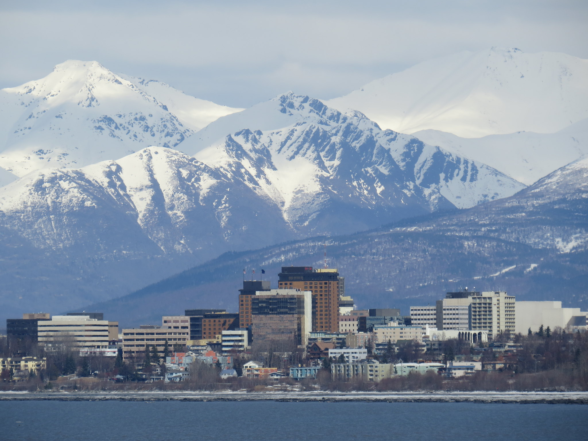 Photo of downtown Anchorage, with the Chugach Mountains in the background.