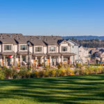 Row of tan townhouses with a green manicured lawn in the foreground, Mt. Hood in the background to the right